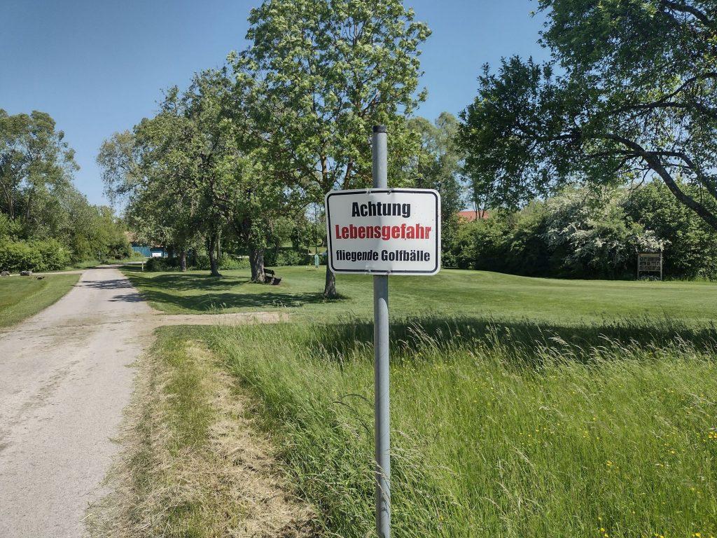 Schild: Achtung Lebensgefahr - fliegende Golfbälle / Sign: Attention danger to life - flying golf balls